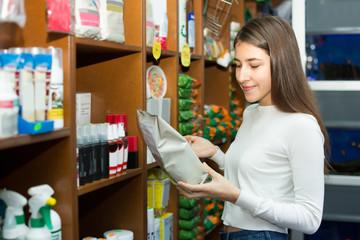 Girl watching dry food in pet store.