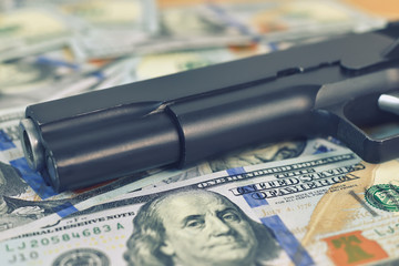 black gun  on dollar bills