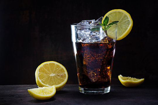 glass of cola or ice tea with lemon slices and peppermint garnis
