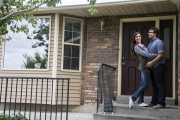 new home owners on front door steps of new home as dog looks out window