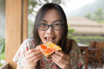 Woman eating bread with jam