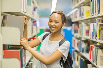 african college girl looking for book in school library