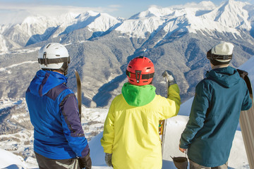 Group of snowboarders and skier at summit