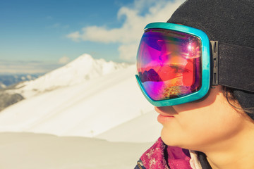Girl dressed in ski or snowboard fashion mask goggles
