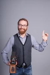 Stylishly dressed photographer with retro camera