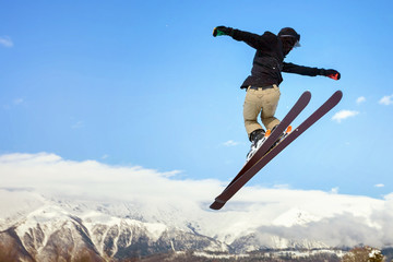 Skier doing high jump above the mountain