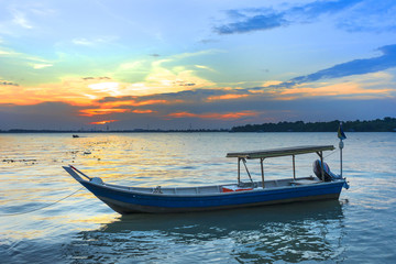 Wooden fisherman boat with sunset background