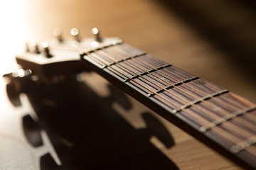 guitar neck with string on blurred wood background light and sha