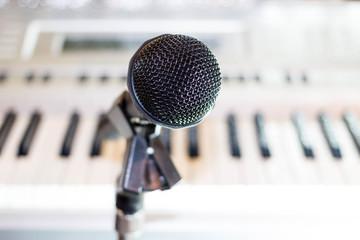 Black microphone on background keys synthesizer