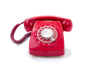 Old and dust red retro phone on white.