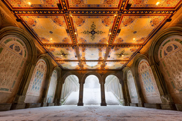 Low angle view of the Bethesda Terrace Arcade during a winter snowstorm with illuminated tile ceiling. Wintertime in Central Park, Manhattan, New York City