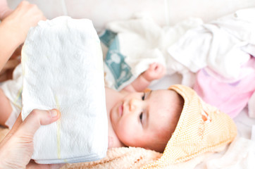 parental hand holds stack of  diapers baby on changing table