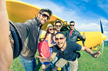 Best friends taking selfie at aeroclub with ultra light airplane - Alternative way of travel to exclusive destinations - Vintage color tones