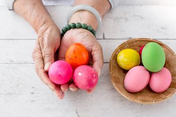 Hands holding easter eggs basket on wooden table.