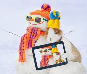 Little rabbit in a hat taking a selfie with funny dressed snowman