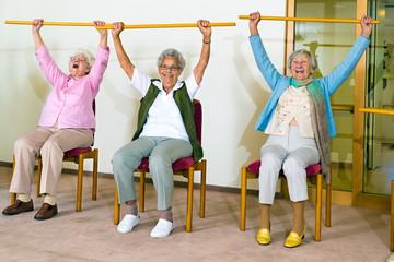 Three happy elderly ladies doing exercises.