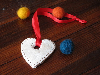 Cookie in the form of heart with red ribbon near three colored felt balls on wooden boards