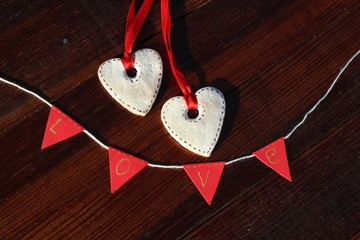 "Two cookies in the form of hearts with red ribbon on wooden brown boards with inscription ""Love"""