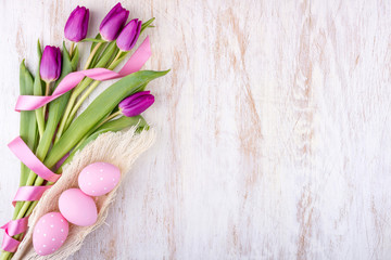 easter eggs and flowers over white wooden table