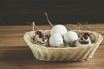 eggs in a wicker basket on a wooden table , toned