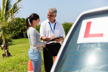 Fototapete - female learner driver and instructor