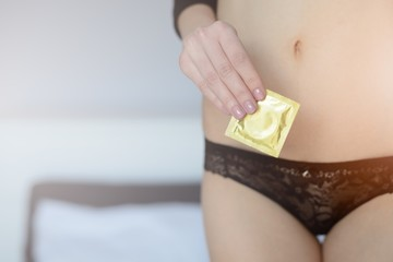 Close-up of woman holding condom packet in her hand.