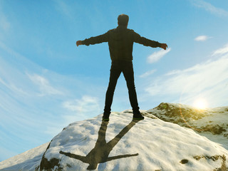 man with open arms over a mountain