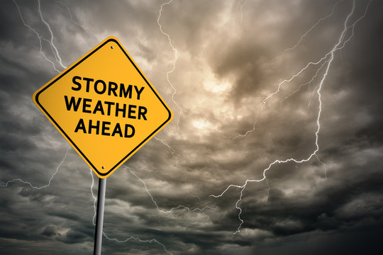 Sign with words 'Stormy weather ahead' and thunderclouds