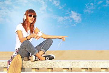 pretty girl listens to music using smartphone and headphones and skateboard by her side