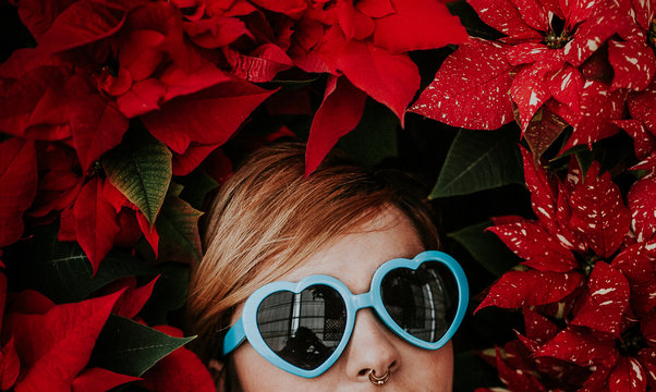 Woman with Blue Heart-Shaped Sunglasses Covered with Poinsettia