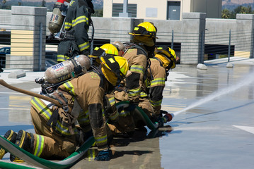 Firefighters training for fire with water hose