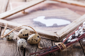 Quail eggs and willow,a rabbit in wooden frame,the symbol of Easter on the aged wooden background.selective focus