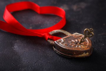 Padlock with key and a red ribbon ,the symbol of love.The background to the Valentine's day.selective focus.
