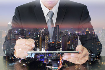Double exposure of businessman working with tablet and night city