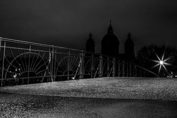 Kabelsteg über die Isar bei Nacht - im Hintergrund St. Lukas (schwarzweiß)