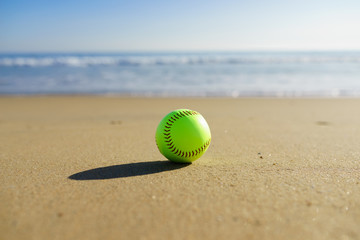 Softball at a California beach with white wave in pacific ocean