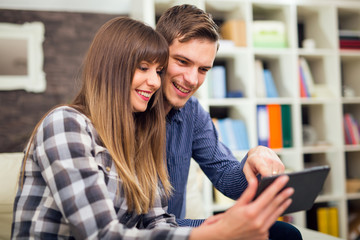 Attractive couple using tablet together on sofa at home.
