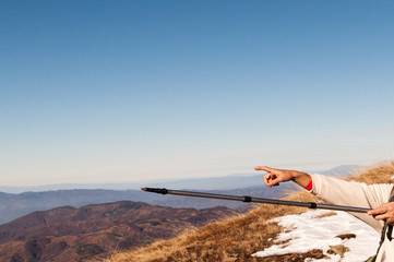Hikers pointing with hiking pole and hand on the mountain