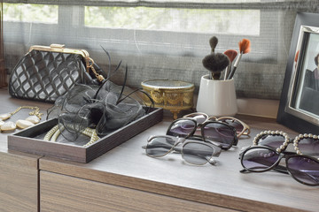 handbag,sunglasses,jewelry and makeup brushes on a wooden dressing table