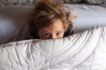 Bambina gioca a letto sotto il piumone