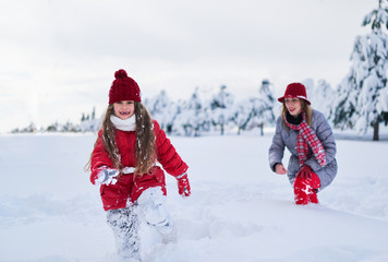 Mother walks with her daughter in  snowy winter park
