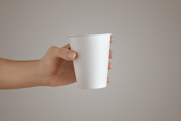 Woman hand holds paper glass isolated white