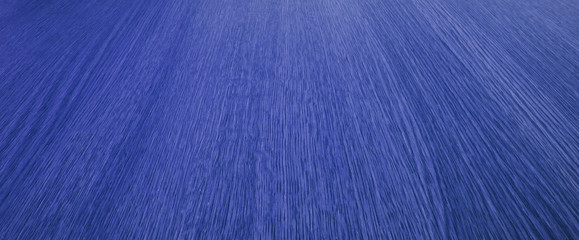 Bright blue background texture, converging lines, wood grain.