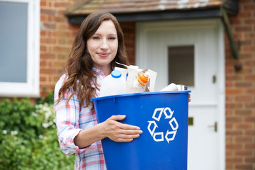 Portrait Of Woman Carrying Recycling Bin