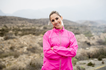 young attractive sport woman in running jacket posing with attitude defiant cool