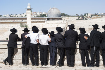A group of Ultra Orthodox Jews, yeshiva students standing in front of the Western Wall, Temple Mount and Al Aqsa mosque. Temple Jerusalem, the Old city of Jerusalem, Israel.