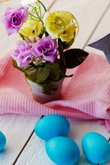 Easter blue Easter background with eggs and flowers on white wooden background