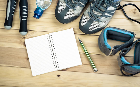 Skipping Rope, Ankle Weights, Sport Shoes, Bottle Of Water And Notepad To Workout Plan On Wooden Table. Sport Fitness Background