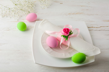Pink and green Easter table place setting with plate, napkin, pink and green Decorated Easter eggs on white wooden background