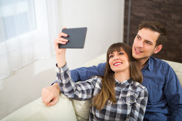 Marriage or couple laughing and taking a selfie with phone sitting on a couch at home